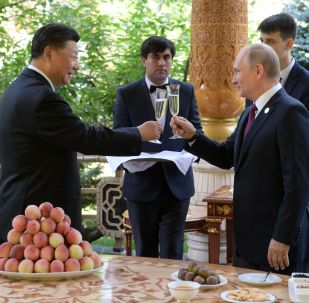Russian President Vladimir Putin Gives Birthday Present to Chinese President Xi Jinping during the Conference on Interaction and Confidence-Building Measures in Asia