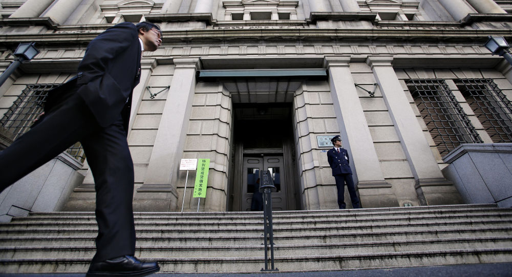 In this Nov. 19, 2014 file photo, a man walks by the Bank of Japan headquarters in Tokyo