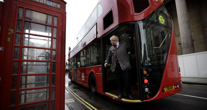 Boris Johnson (the then Mayor of London) rides on the back of a prototype new design London double-decker bus in 2011