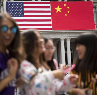 In this Thursday, 24 September 2015, photo, China's flag is displayed next to the American flag on the side of the Old Executive Office Building on the White House complex in Washington, the day before a state visit by Chinese President Xi Jinping