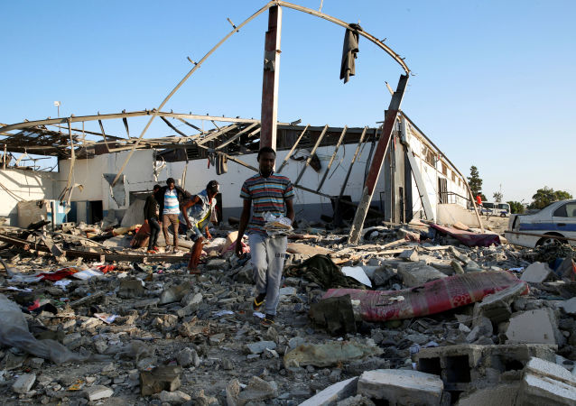 Migrants carry the remains of their belongings from among rubble at a detention centre for mainly African migrants that was hit by an airstrike in the Tajoura suburb of the Libyan capital of Tripoli, Libya July 3, 2019