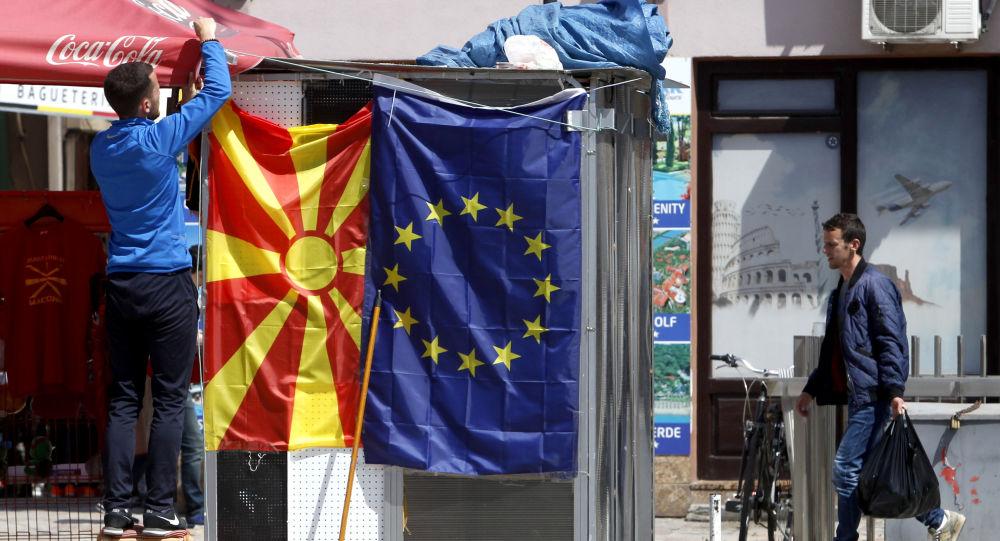 A street vendor fixes a North Macedonia flag next to an EU flag in a street in Skopje