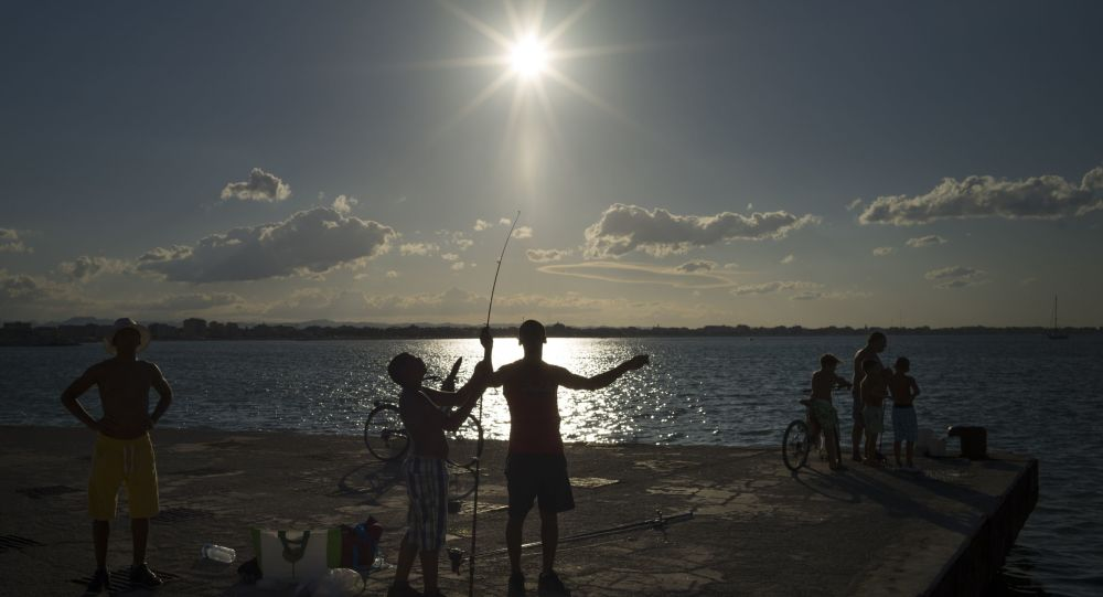 Fishermen prepare for fishing during a sun set on the pier in Rimini, Italy, Friday, Sept. 1, 2017.