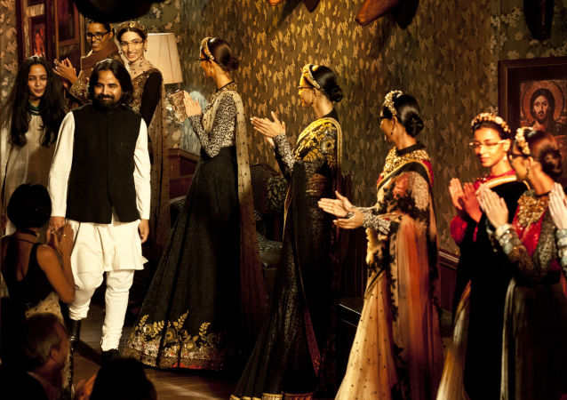 Models wearing new creations by Indian fashion designer Sabyasachi Mukherjee (L) applaud him at the end of a fashion show in New Delhi on August 12, 2012