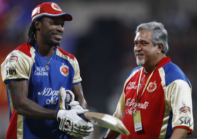 Royal Challengers Bangalore team owner Vijay Mallya, right, shares a light moment with cricketer Chris Gayle as the rain delayed the start of the Indian Premier League (IPL) cricket match between Royal Challengers Bangalore and Chennai Super Kings' in Bangalore, India, Wednesday, April 25, 2012