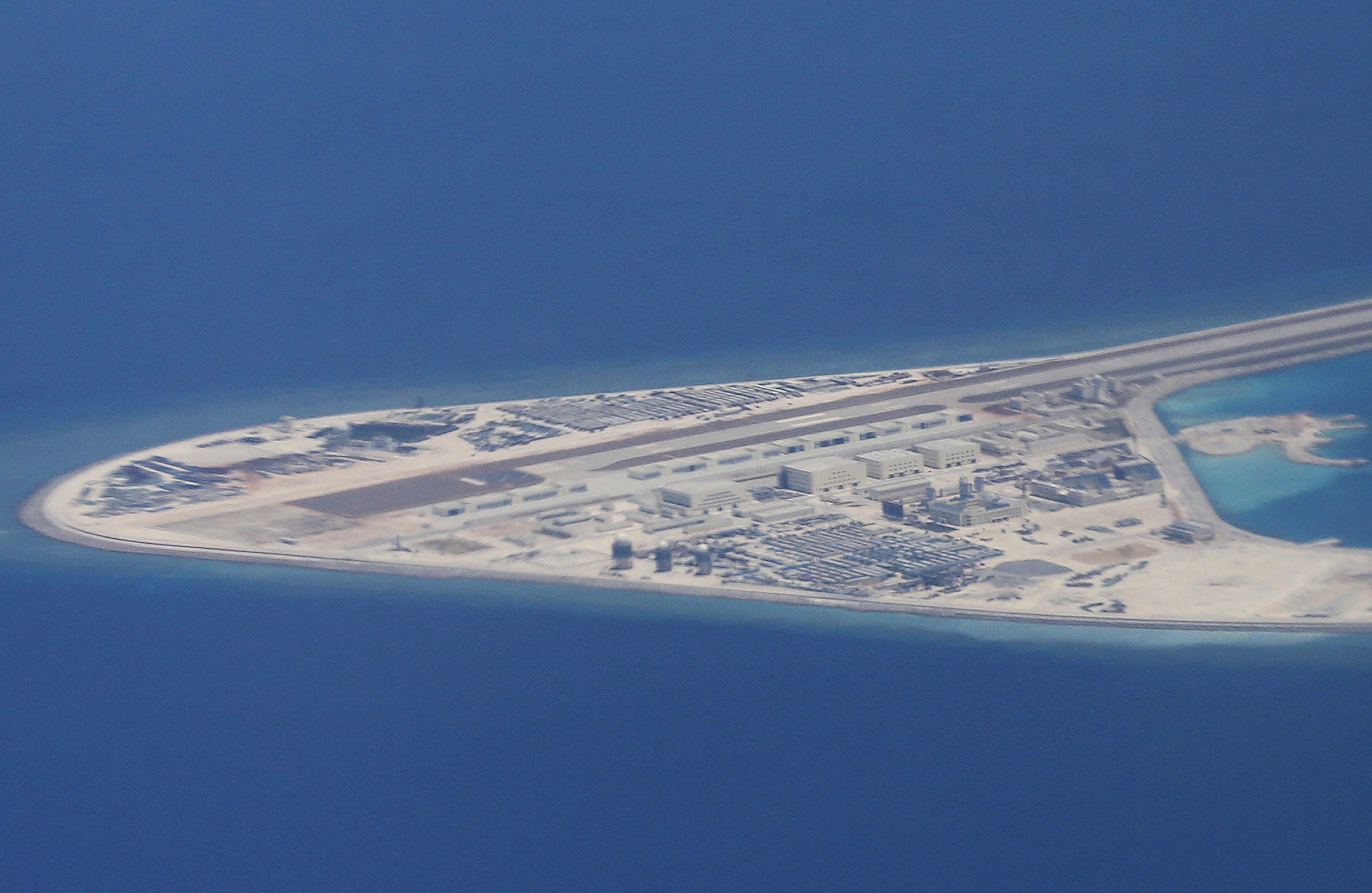 Chinese structures and an airstrip on the man-made Subi Reef at the Spratly group of islands in the South China Sea are seen from a Philippine Air Force C-130 transport plane of the Philippine Air Force, Friday, April 21, 2017