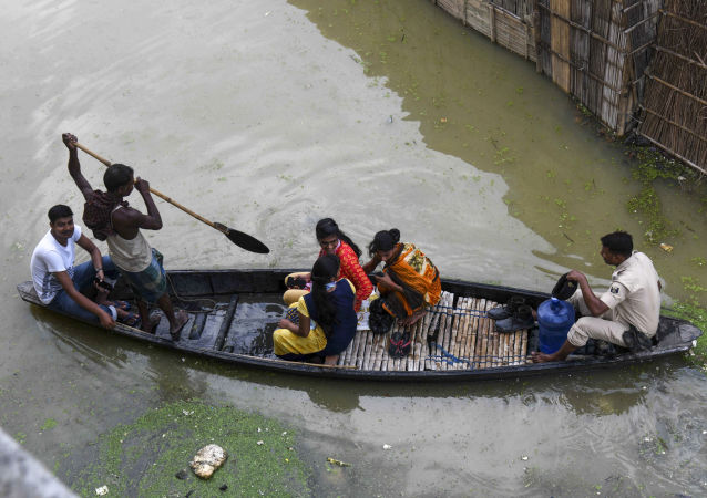 An Indian policeman travels with residents on a wooden boat to cross a flooded locality near the Ahiyapur police station at Muzaffarpur district in the Indian state of Bihar on July 18, 2019