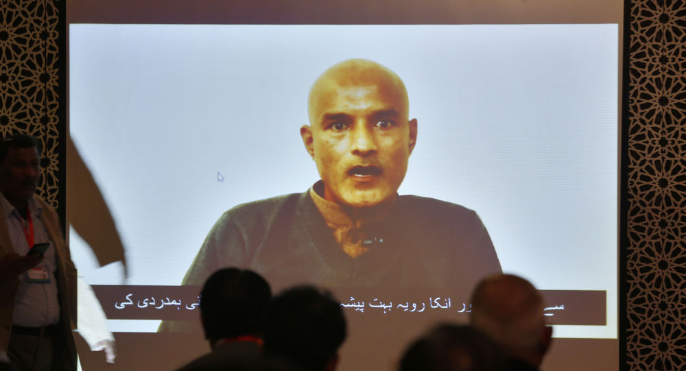 Pakistani journalists watch a video message of imprisoned Indian naval officer Kulbhushan Jadhav