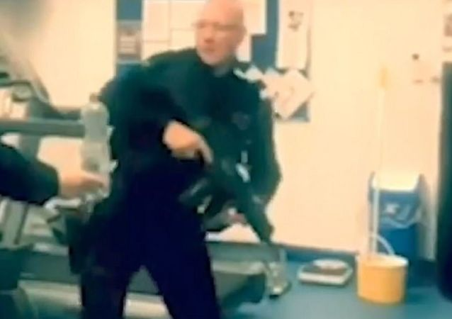 In the clip, the nuclear police officer can be seen brandishing his assault weapon while another officer holds up a water bottle