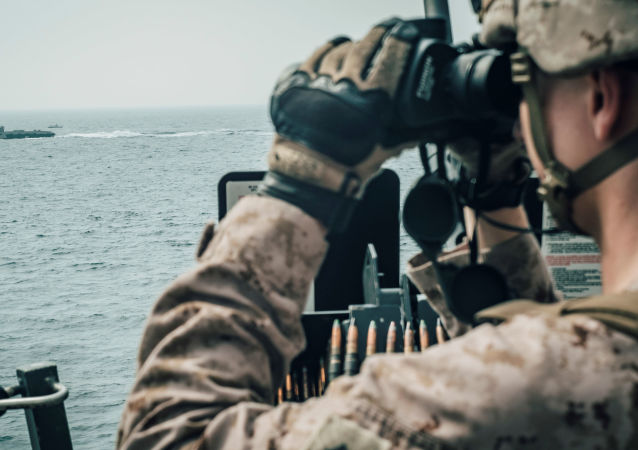 A U.S. Marine observes an Iranian fast attack craft from USS John P. Murtha during a Strait of Hormuz transit, Arabian Sea off Oman