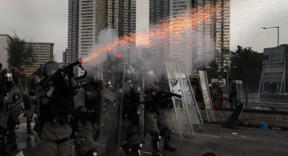 A riot police fires tear gas during a confrontation with protesters on Monday, Aug. 5, 2019. Droves of protesters filled public parks and squares in several Hong Kong districts on Monday in a general strike staged on a weekday to draw more attention to their demands that the semi-autonomous Chinese city's leader resign.