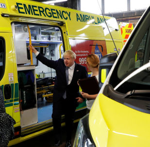 Britain's Prime Minister Boris Johnson holds on to an ambulance during a visit to Pilgrim Hospital in Boston, Britain August 5, 2019