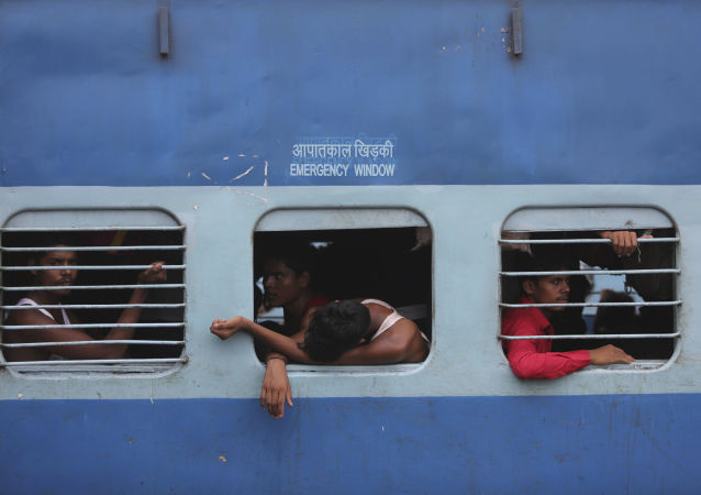 Indian migrant laborers sit inside a train as they prepare to leave the region, at a railway station in Jammu, India, Wednesday, Aug. 7, 2019