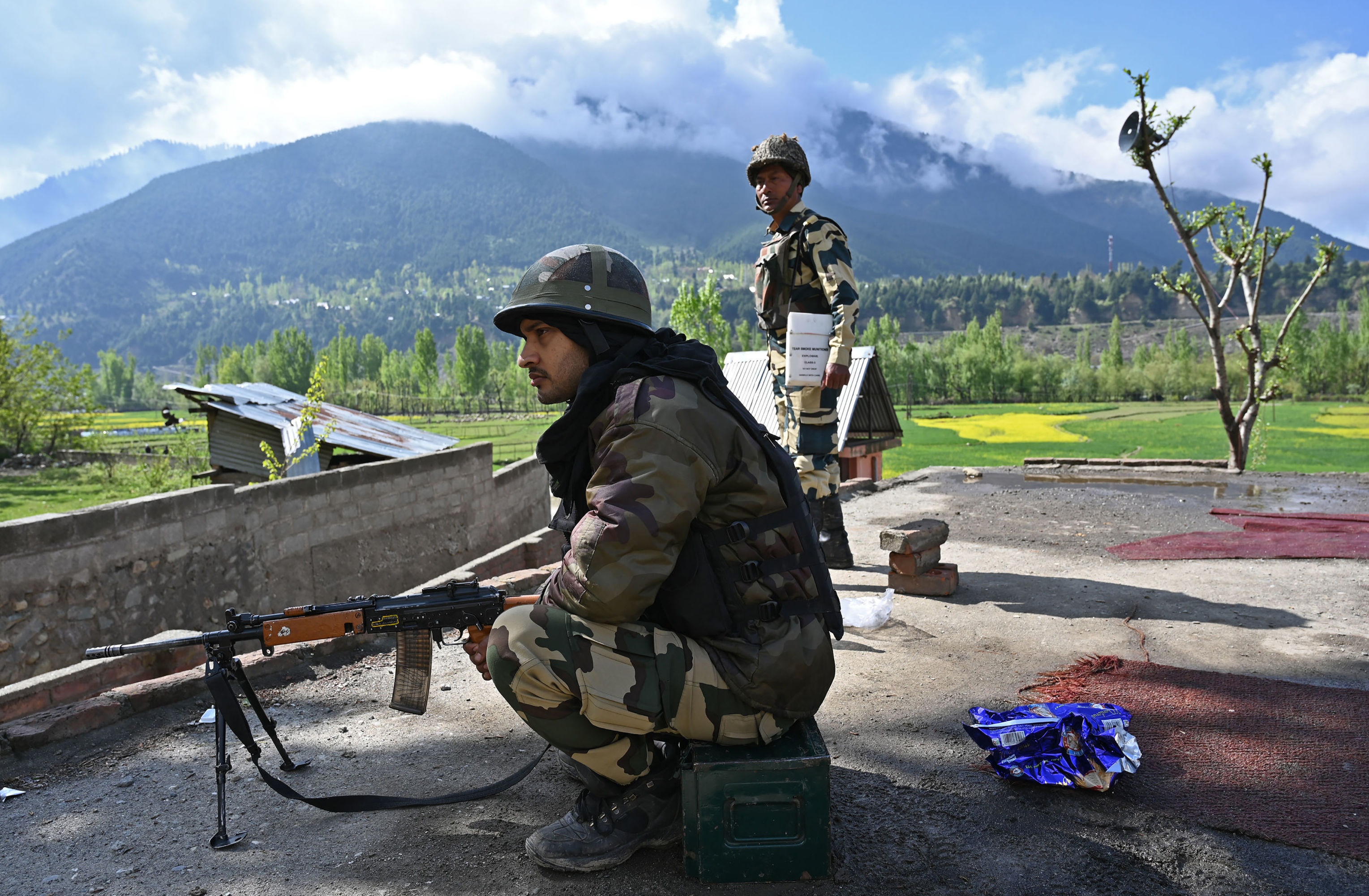 Indian Border Security Force (BSF) soldiers stand guard on the top of a polling station during a second phase of elections at Kangan, some 35 km from Srinagar on April 18, 2019