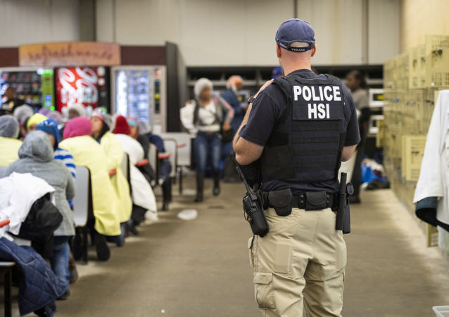 Homeland Security Investigations (HSI) officers from Immigration and Customs Enforcement (ICE) look on after executing search warrants and making some arrests at an agricultural processing facility in Canton