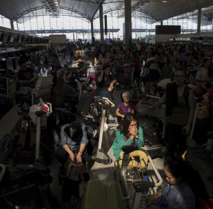A beam of sunlight is cast on the travellers as they wait at the check-in counters in the departure hall of the Hong Kong International Airport in Hong Kong, Tuesday, Aug. 13, 2019. Protesters clogged the departure area at Hong Kong's reopened airport Tuesday, a day after they forced one of the world's busiest transport hubs to shut down entirely amid their calls for an independent inquiry into alleged police abuse.