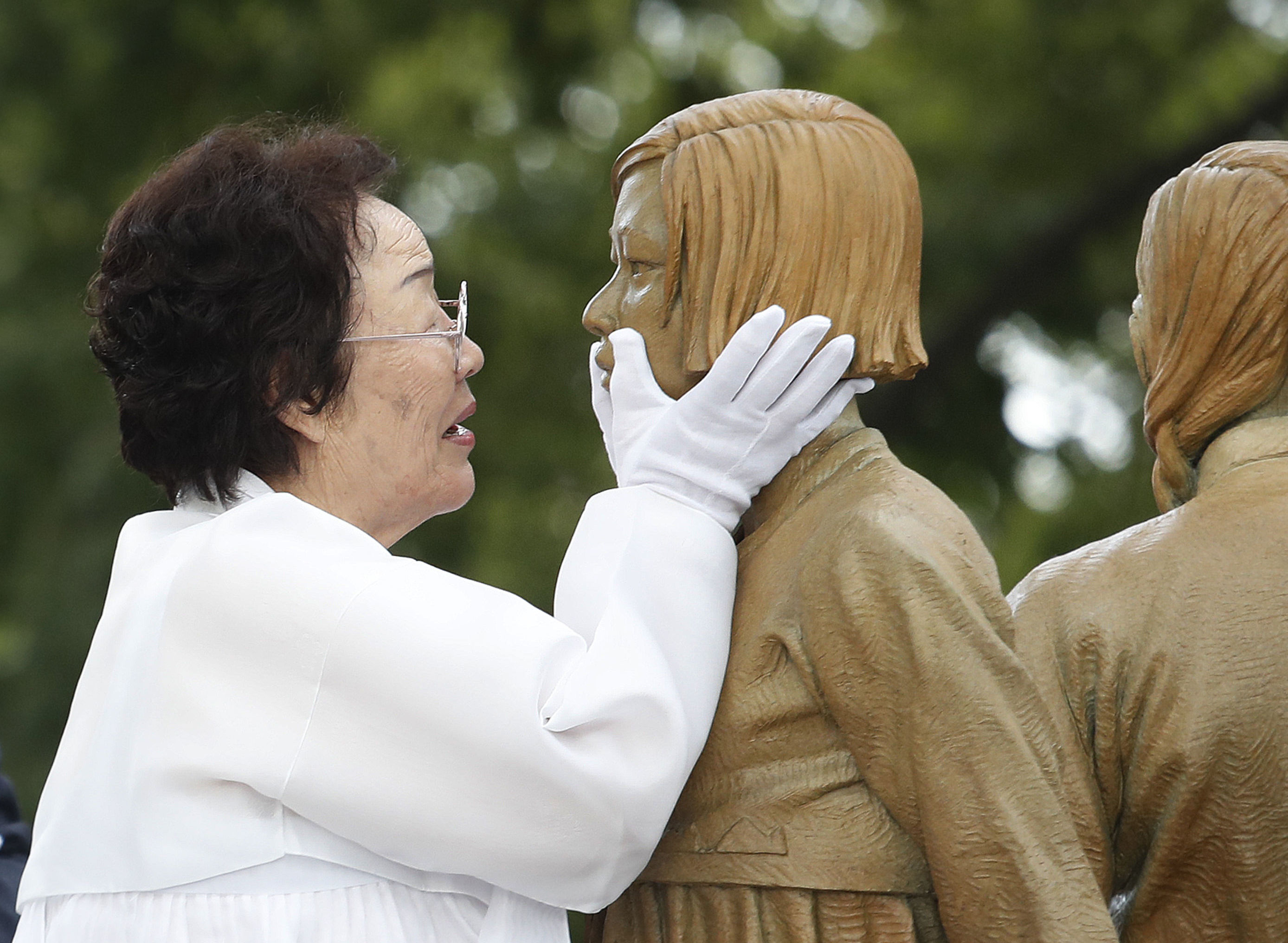 Lee Yong-soo who was forced to serve for the Japanese troops as a sex slave during World War II, touches the face of a statue of a girl symbolising the issue of wartime comfort women during its unveiling ceremony in Seoul, South Korea, Wednesday, Aug. 14, 2019.
