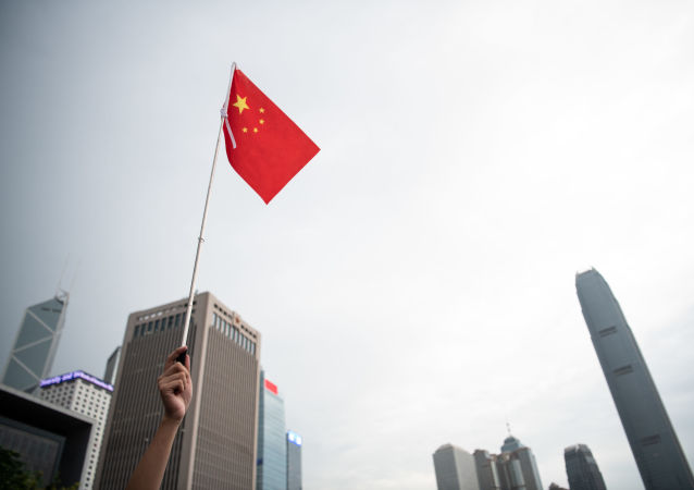 A Chinese flag is held at a rally in support of the police in Tamar Park outside the government headquarters in Hong Kong on July 20, 2019.
