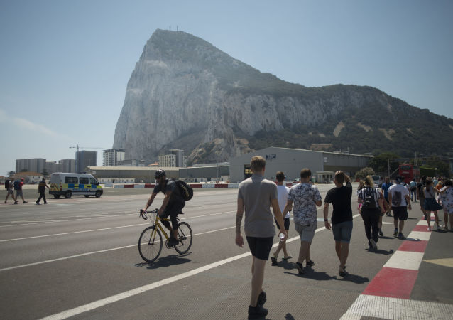 A man rides a bicycle with the Rock of British Colony of Gibraltar in the background, in Gibraltar on August 15, 2019.