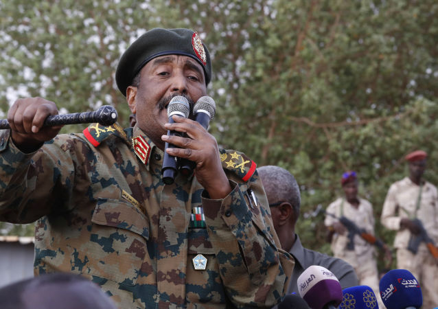 In this June 29, 2019, file photo, Sudanese Gen. Abdel-Fattah Burhan, head of the military council, speaks during a military-backed rally, in Omdurman district, west of Khartoum, Sudan. An African Union envoy says Sudan's ruling military council and the country's pro-democracy movement have reached a power-sharing agreement, including a timetable for a transition to civilian rule. Mohammed el-Hassan Labat said early Friday, July 5, that both sides agreed to form a joint sovereign council that will rule the country for three years or a little more. The sides agreed to five seats for the military and five for civilians with an additional seat going to a civilian with military background.