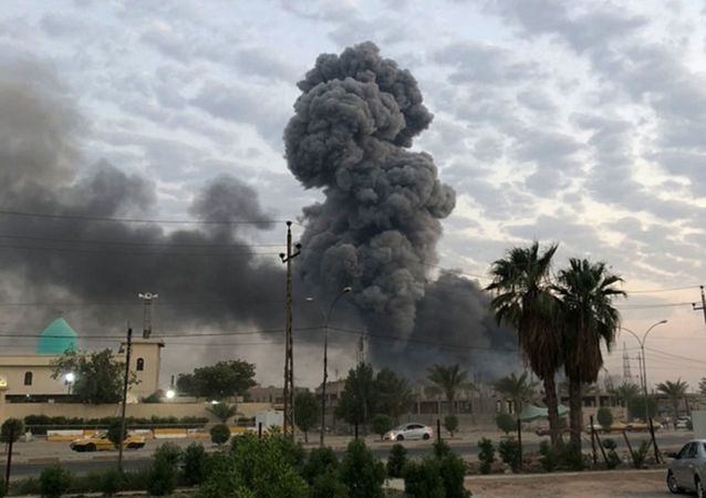 In this Monday, Aug. 12, 2019 file photo, plumes of smoke rise after an explosion at a military base southwest of Baghdad, Iraq. A fact-finding committee appointed by the Iraqi government to investigate a massive munitions depot explosion near the capital Baghdad has concluded that the blast was the result of a drone strike. A copy of the report was obtained by The Associated Press Wednesday, Aug. 21, 2019