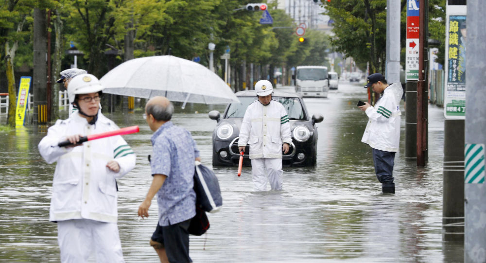 Police officers check a submerged street at a flooded area in Saga, Saga prefecture, southern Japan August 28, 2019, in this photo taken by Kyodo.