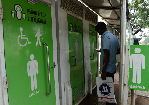 An Indian resident checks his phone as he waits to use a public toilet on a street in  Chennai on November 15, 2017