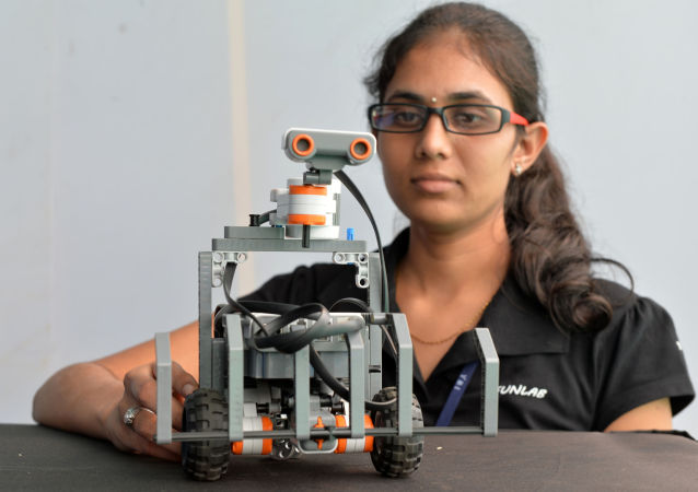An Indian volunteer demonstrates the functioning of a motion sensing robot at a stall on the inaugural day of the 10-day Edinburgh International Science Festival, in Bangalore on August 30, 2013
