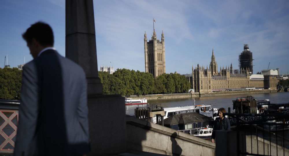 A pedestrian walks up a staircase on the southern bank of the River Thames with Houses of Parliament seen in the background in London on September 2, 2019