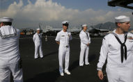 U.S. Navy sailors stand on the deck of the USS Ronald Reagan aircraft carrier in Hong Kong, Wednesday, Nov. 21, 2018