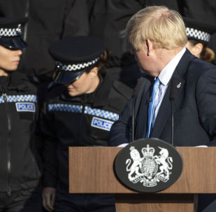 Britain's Prime Minister Boris Johnson (R) reacts as a student police officer appears to feel unwell as she stands behind the prime minister as he takes questions from members of the media during a visit with the police in West Yorkshire, northern England, on September 5, 2019