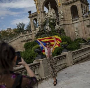 An Ukranian tourist poses for a snapshot with a Catalan independence flag during the Catalan National Day in Barcelona, Spain, Wednesday, Sept. 11, 2019