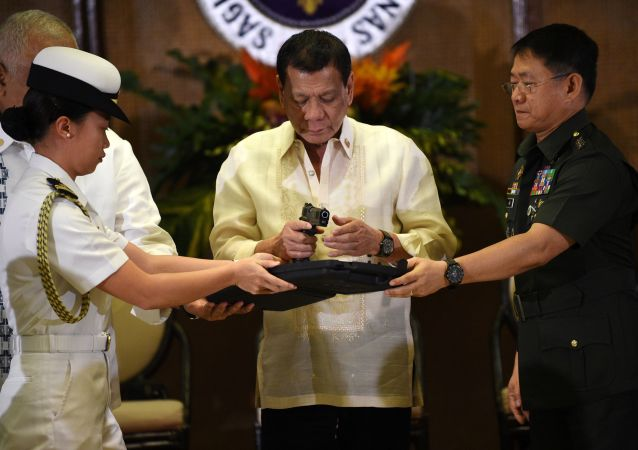 Philippine President Rodrigo Duterte (C) holds a .45 caliber handgun, one of 3,000 units handed over during a ceremonial turn-over to the military, at Malacanang Palace in Manila on July 18, 2017