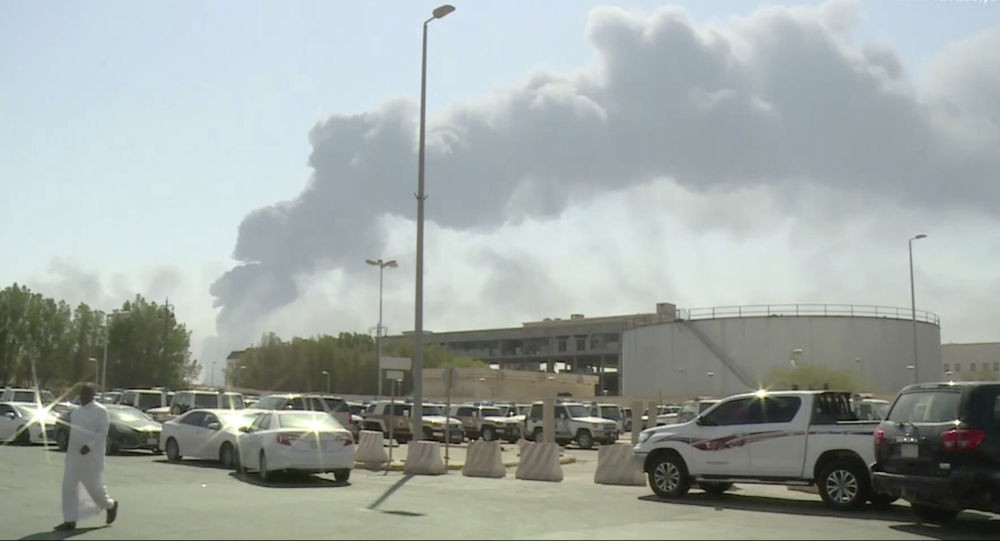 In this image made from a video broadcast on the Saudi-owned Al-Arabiya satellite news channel on Saturday, Sept. 14, 2019, a man walks through a parking lot as the smoke from a fire at the Abqaiq oil processing facility can be seen behind him in Buqyaq, Saudi Arabia. Drones launched by Yemen's Houthi rebels attacked the world's largest oil processing facility in Saudi Arabia and another major oilfield Saturday, sparking huge fires at a vulnerable chokepoint for global energy supplies