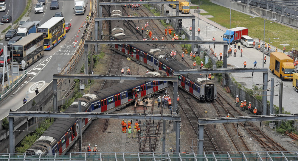 Staffs members of MTR Corp. stand around an derailed train near Hung Hom station in Hong Kong, Tuesday, Sept. 17, 2019