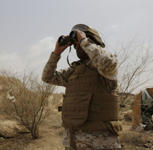 A Saudi soldier looks with binoculars toward the border with Yemen in Jazan, Saudi Arabia, Monday, April 20, 2015