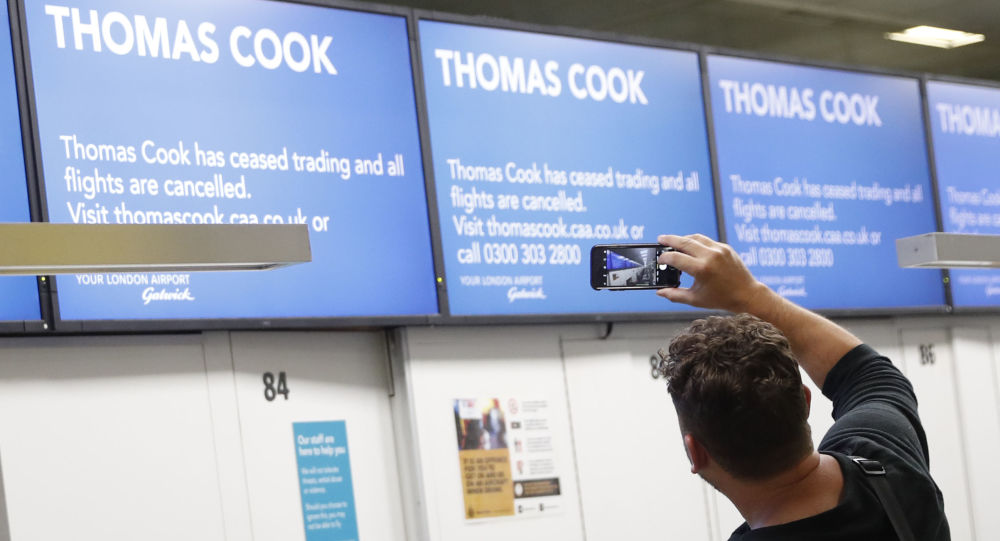 John Garret from Boston Ma., who was supposed to be flying to Malta, takes a photo of the empty Thomas Cook check in desks in Gatwick Airport, England Monday, Sept. 23, 2019.