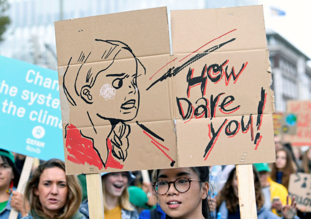 An activist holds a drawing depicting Swedish environmentalist Greta Thunberg during a protest march to call for action against climate change, in The Hague, The Netherlands, 27 September 2019