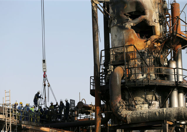 Workers are seen at a damaged Saudi Aramco oil facility in Abqaiq, Saudi Arabia, 20 September 2019