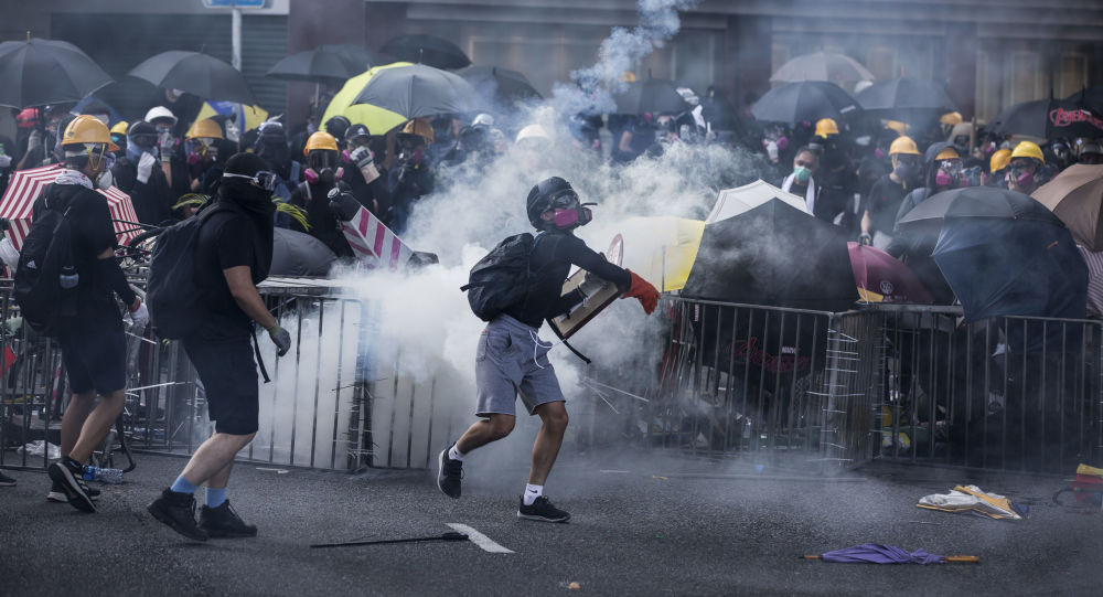 Protesters react among tear gas fired by police in the Sha Tin district of Hong Kong on October 1, 2019, as the city observes the National Day holiday to mark the 70th anniversary of communist China's founding