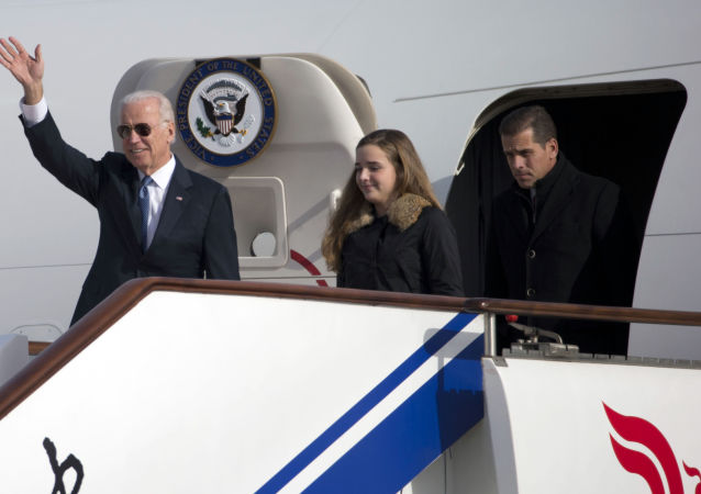 US Vice President Joe Biden waves as he walks out of Air Force Two with his granddaughter, Finnegan Biden (C) and son Hunter Biden (R) upon their arrival in Beijing on December 4, 2013.