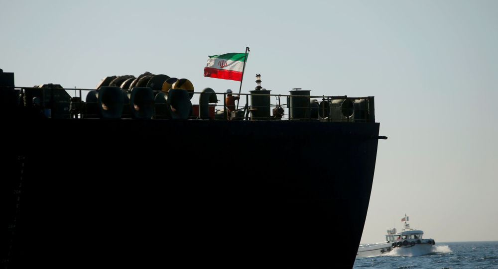 A crew member raises the Iranian flag at Iranian oil tanker Adrian Darya 1, formerly named Grace 1, as it sits anchored after the Supreme Court of the British territory lifted its detention order, in the Strait of Gibraltar, Spain, August 18, 2019