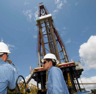 Workers stand near an oil drilling rig belonging to Petroamazonas at Miranda Port in Tiputini