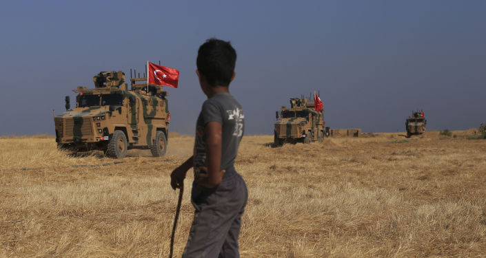A Turkish n armored vehicles patrol as they conduct a joint ground patrol with American forces in the so-called safe zone on the Syrian side of the border with Turkey, near the town of Tal Abyad, northeastern Syria, Friday, Oct.4, 2019