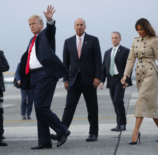President Donald Trump, left, waves as he walks to his vehicle with Melania Trump, right, during their arrival on Air Force One at Melsbroek Air Base, Tuesday, July 10, 2018 in Brussels, Belgium. Walking with them is Ambassador Gordon D. Sondland, center