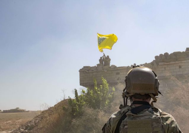 In this Sept. 21, 2019, photo, released by the U.S. Army, a U.S. soldier oversees members of the Syrian Democratic Forces as they demolish a Kurdish fighters' fortification and raise a Tal Abyad Military Council flag over the outpost as part of the so-called safe zone near the Turkish border.