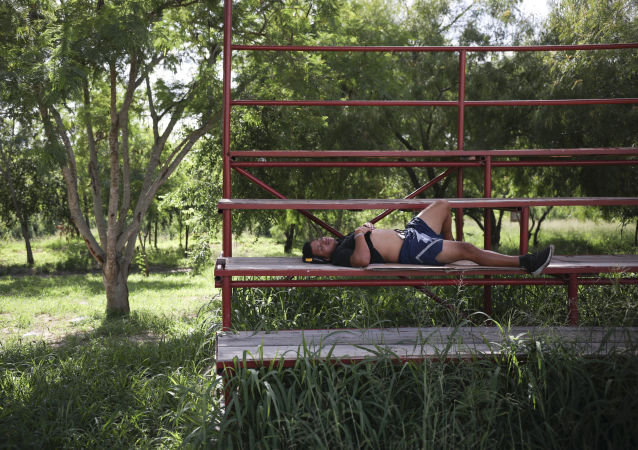 A migrant rests in a park near the entrance to the Puerta Mexico bridge that crosses over the Rio Grande river in Matamoros, Mexico