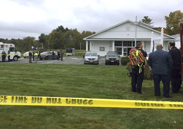 In this photo provided by WMUR-TV, police stand outside the New England Pentecostal Church after reports of a shooting on Saturday, Oct. 12, 2019, in Pelham, N.H.