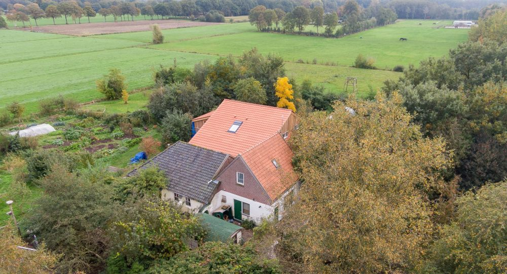 This aerial picture taken on October 15, 2019 shows a farmhouse in a remote area of northern Netherlands' province of Drenthe, near the village of Ruinerwold, where Dutch police discovered a hidden staircase behind a cupboard leading to a cellar where a man and five others believed to be his children aged between 18 and 25 were hidden and reportedly spent years waiting for the end of time, officials said. - Local media said the family were found after one of the sons went to a nearby pub in a confused state, drank five beers and then asked for help, saying he had not been outside for nine years.