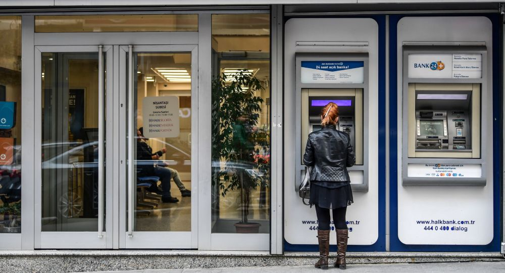 A woman uses an ATM machine at a branch of Turkish bank Halkbank on December 1, 2017 in Istanbul.